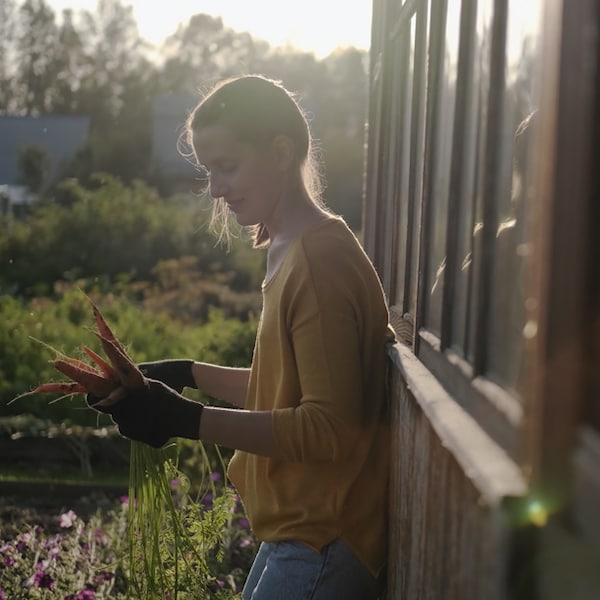 A woman leaning against a wall outside with gardening gloves on.