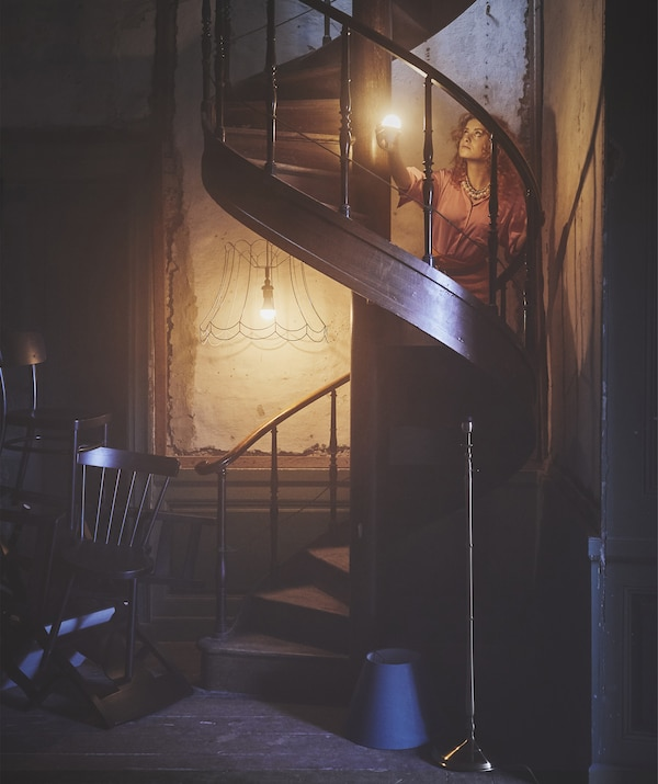 A woman lighting her way up a wooden spiral staircase in a dark room with an illuminated bulb.