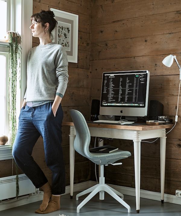 A woman looks out of a window in the corner of a room that has been made into a home office with desk and swivel chair.