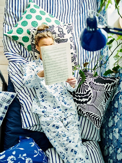 A woman lying in bed with cushions, bed linen and wallpaper with different patterns around her, while reading sheet music.