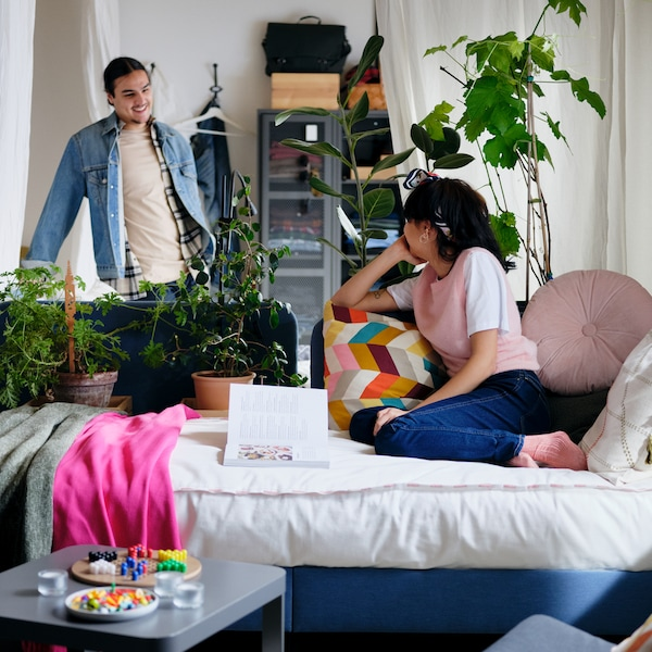 A woman on a blue BLÅKULLEN bed with various colourful cushions and throws, with a man standing behind some plants.