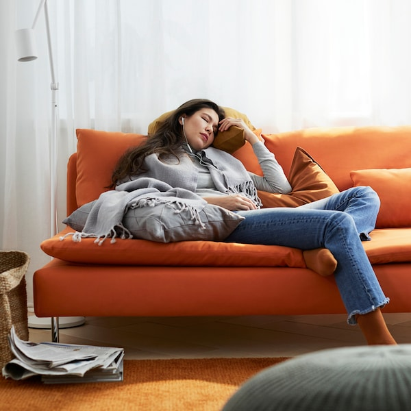 A woman on a sofa in orange, with orange and grey cushions and a grey throw laying on it.