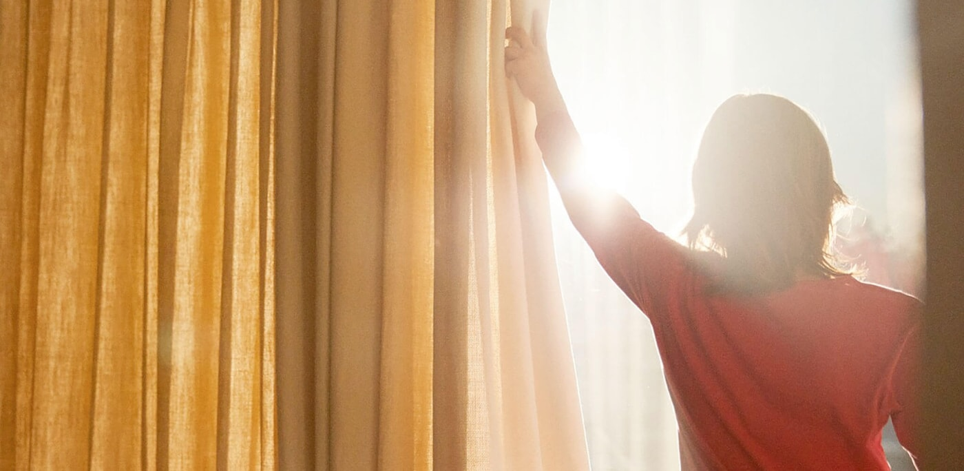A woman opening her golden yellow curtains to let the bright sun stream into her home.