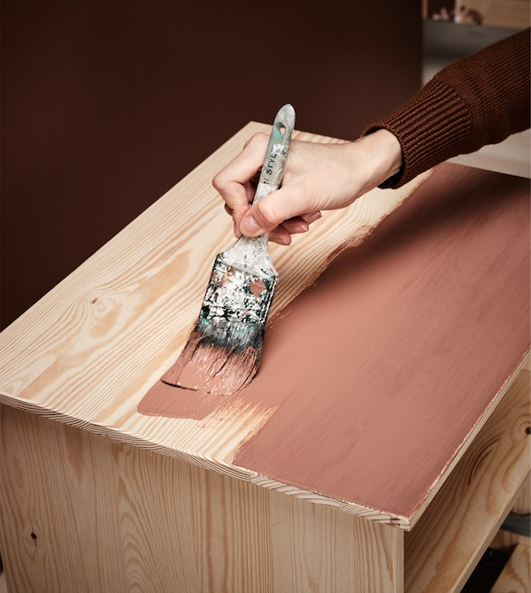 A woman paints a bedside table using a brush and brown paint to give it a new look.