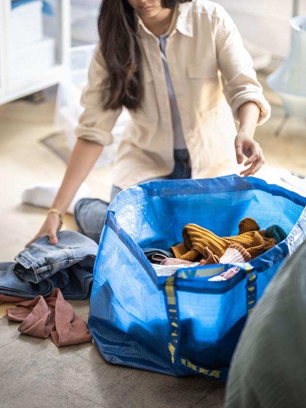 A woman piling clothing into a large, blue, reusable plastic FRAKTA bag.