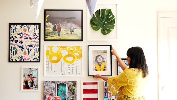 A woman placing a framed photograph on a gallery wall to show to arrange a gallery wall of photos and artwork at home.