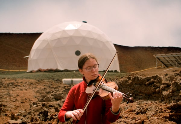 A woman playing violin in front of a white man-made structure in a barren landscape.