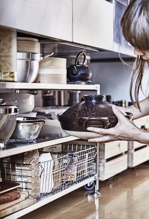 A woman putting a dish on a shelf.