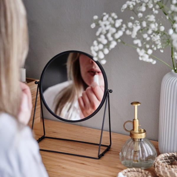 A woman putting on lipstick looking into a dark gray LASSBYN mirror that has a white vase of flowers behind it.