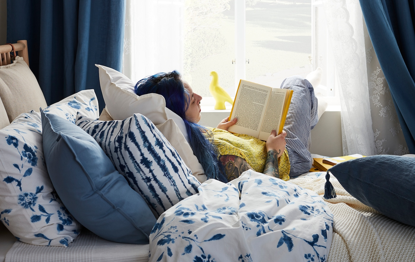 A woman reading a book in bed next to a large window.