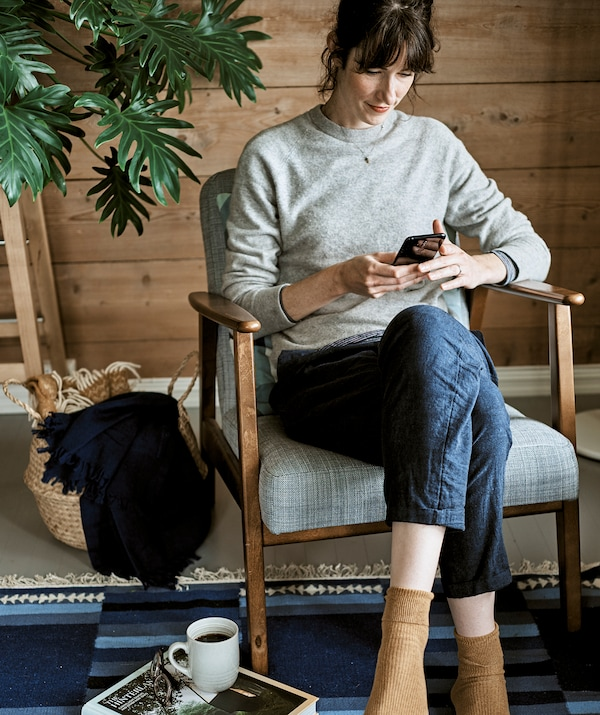 A woman scrolls through her mobile while sitting in a wood-framed armchair with grey upholstery on a blue rug.