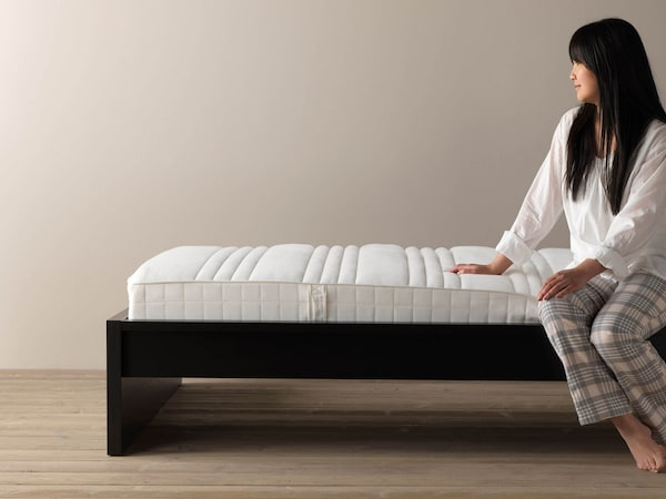 A woman siting on a white memory foam mattress inside a black bed frame.