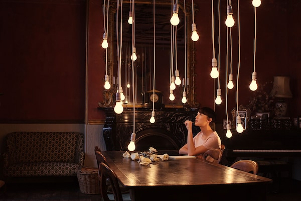 A woman sits at a large, dark wooden table above which many individual light bulbs shine and dreams