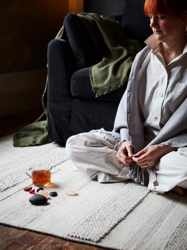 A woman sits on a light colored rug in a living room, with crystals, stones and a glass mug on the floor in front of her.