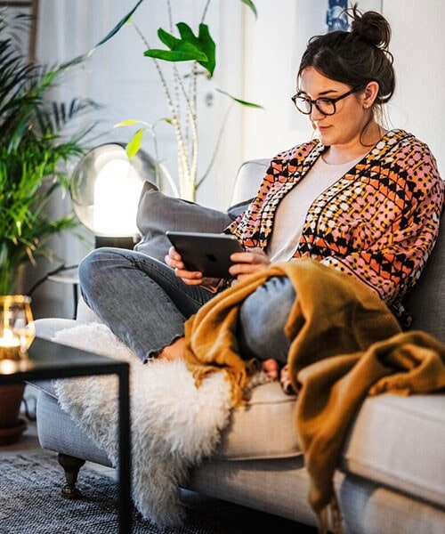 A woman sits with crossed legs on a couch while she uses a tablet device.