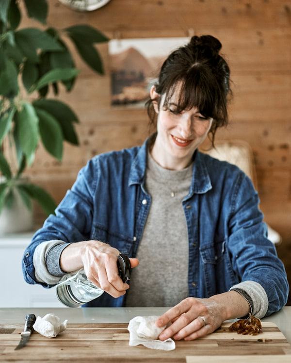 A woman sitting at a kitchen table holding a water spritzer and spraying avocado seeds wrapped in a paper kitchen towel.