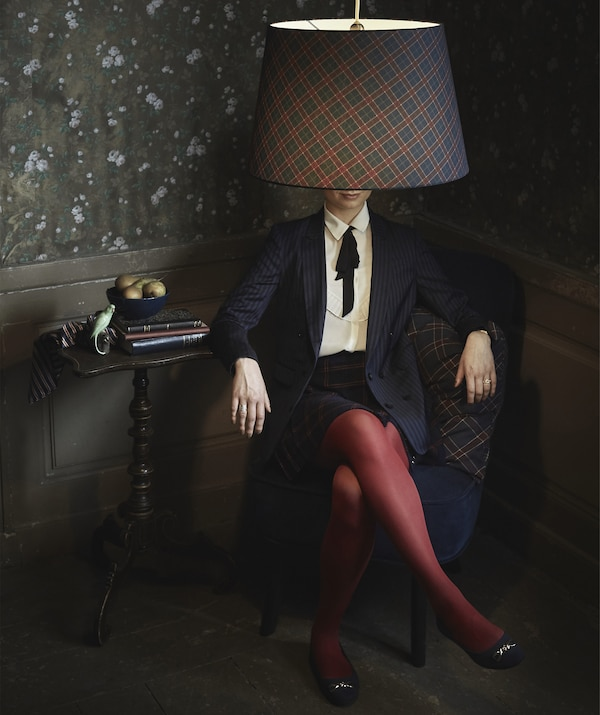 A woman sitting in a chair in a dark room with a chequered-pattern lampshade hanging in front of her face.