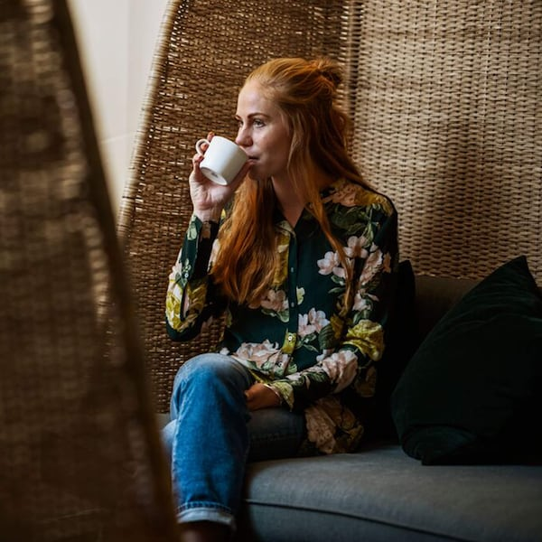 A woman sitting in a floral blouse and jeans sipping UTZ certified coffee from a white mug.
