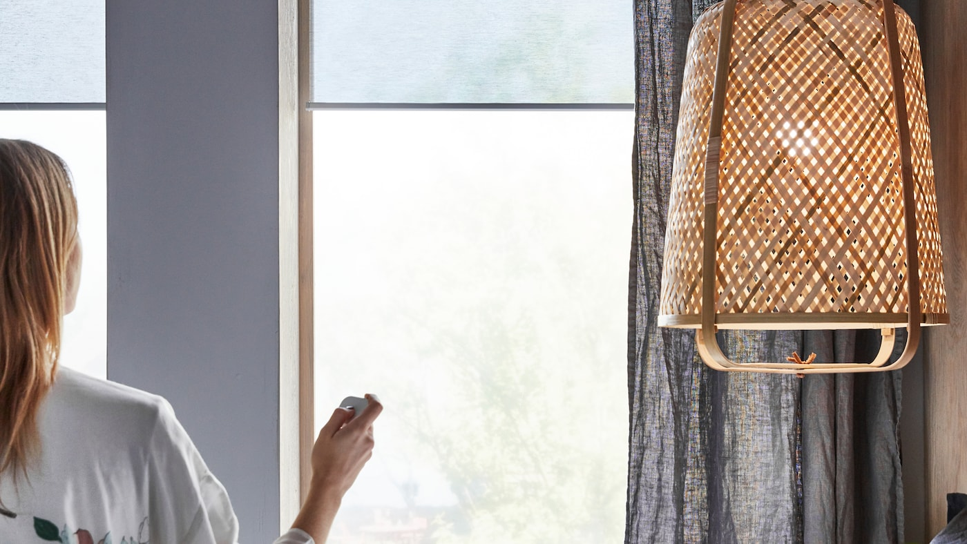 A woman, sitting near a KNIXHULT pendant lamp, uses a remote control on KADRILJ roller blinds hanging in the windows.