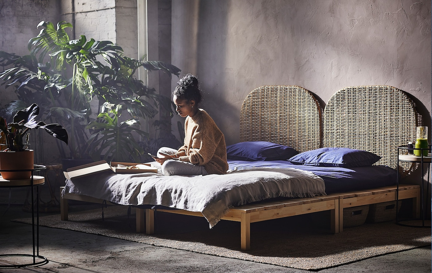 A woman sitting on a platform bed in a room with various plants for decoration.