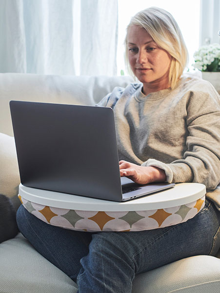 A woman sitting on a sofa typing on her laptop