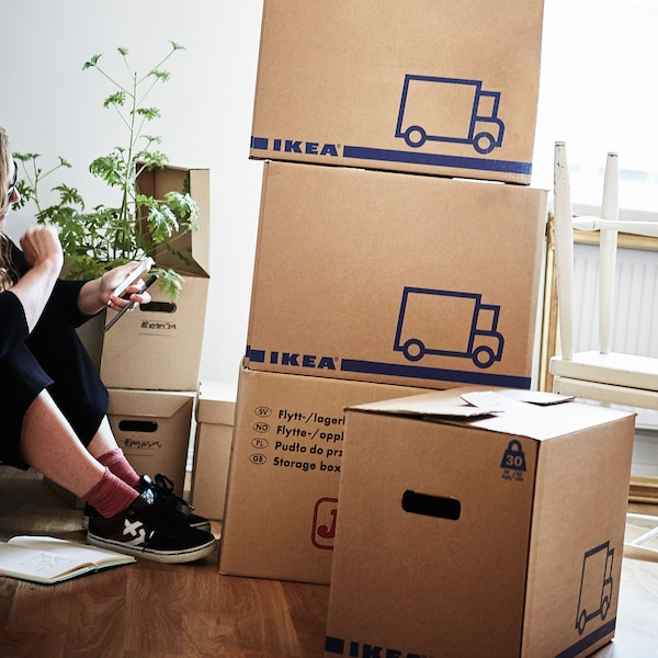 A woman sitting on a wooden floor surrounded by various boxes including a pile of JÄTTENE boxes.