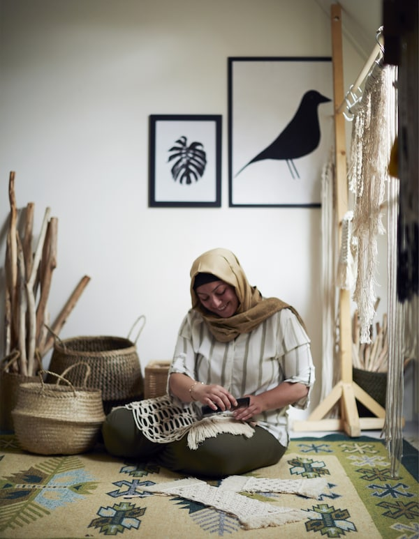 A woman sitting on the floor making macramé creations.