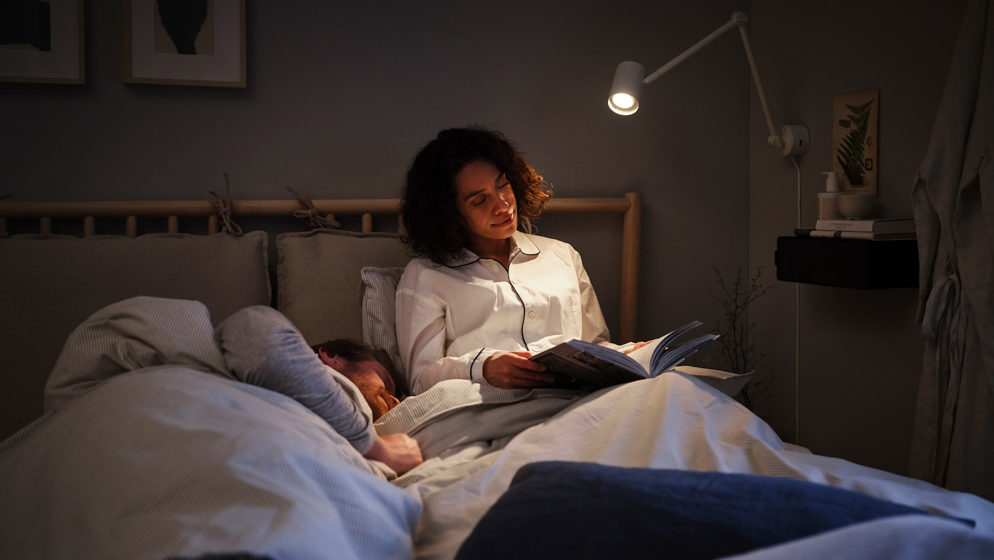 A woman sitting up in bed, reading a book under a reading lamp, with a man lying down in bed beside her.
