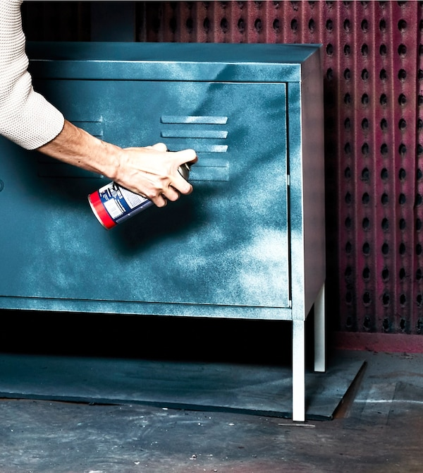 A woman spray paints a white metal IKEA PS cabinet blue to give it a different look.