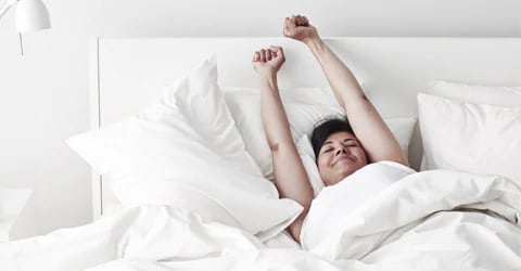 A woman stretch in bed with white duvet covers and pillows.