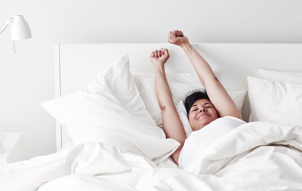 A woman stretching her arms above her head in bed.