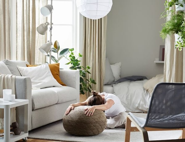 A woman stretching her arms on the floor using SANDARED pouffe shown in a living room with grey sofa and beige curtains.