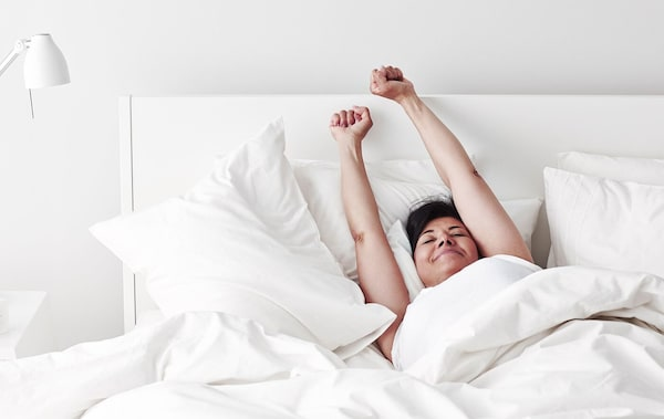 A woman stretching in bed after a good night's sleep.