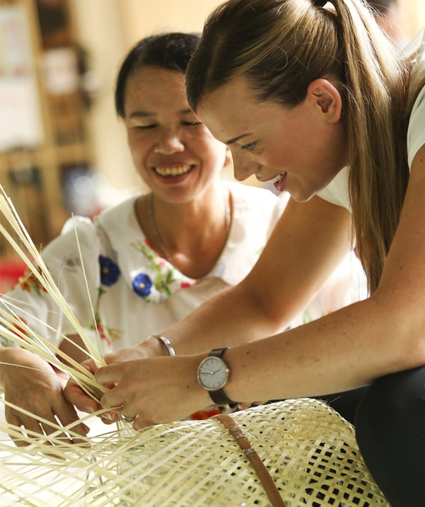 A woman teaching traditional bamboo weaving techniques to Anna Granath.
