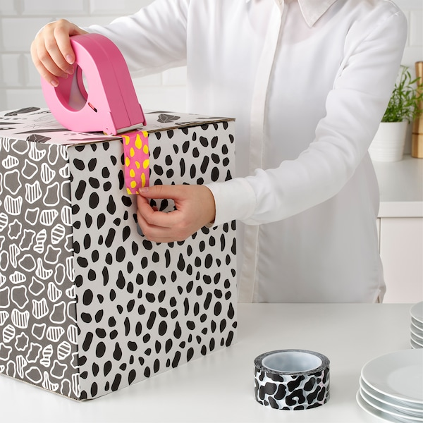 A woman using bright pink and yellow OMBYTE tape to seal a spotted OMBYTE box that is placed on a white surface.