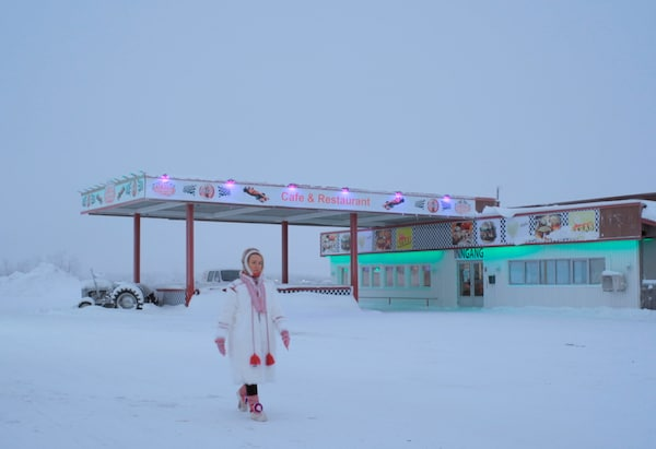 A woman walking through a deserted snowy landscape with a restaurant in the background.
