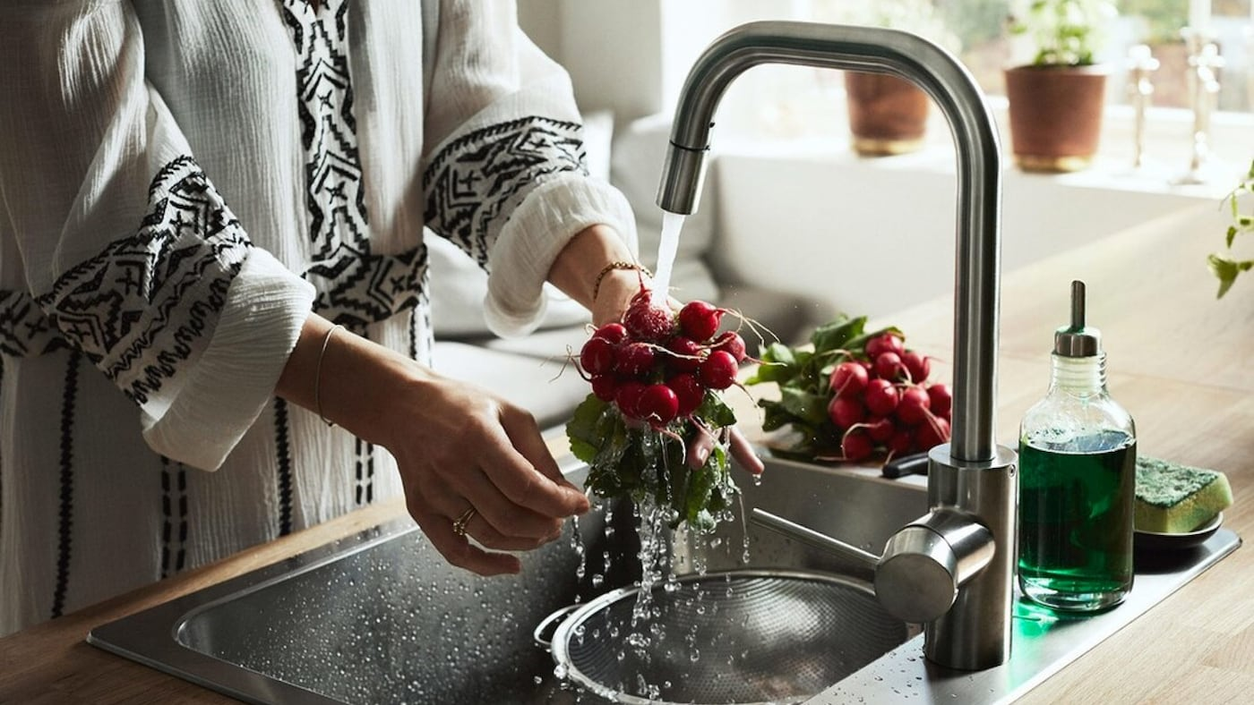 A woman wearing a white kaftan is rinsing a bunch of radishes in a kitchen sink. Another bunch is lying next to the sink.