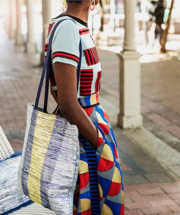 A woman wearing colourful clothes with a blue and yellow tote bag over her shoulder.