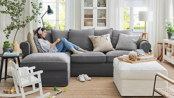 A woman wearing headphones relaxes on a GRÖNLID three-seat sofa with chaise longue in a family living room.