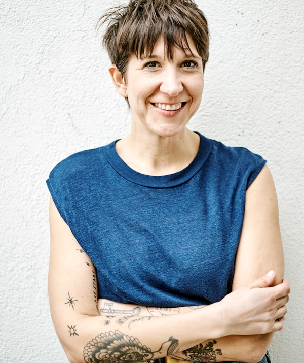 A woman with a brunette pixie cut and tattooed arms, wearing a sleeveless blue T-shirt stands against a white wall.
