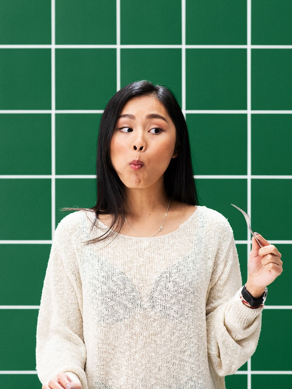 A woman with a white jumper chewing plant balls with an empty fork in her hand in front of a wall of green tiles.