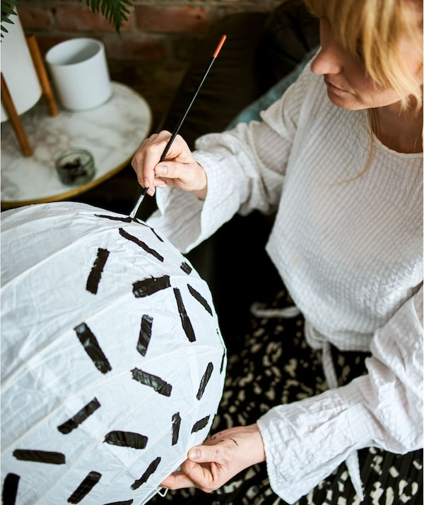 A woman with blonde hair in a white cotton shirt sits and paints a pattern of bold black lines on a white paper lamp shade.