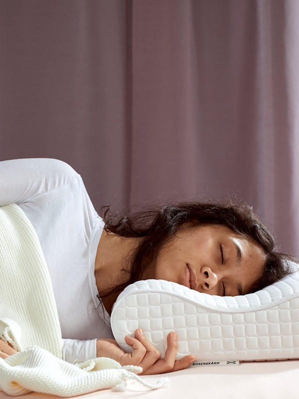 A woman with brown hair and white shirt sleeping under a white blanket on a ROSENSKÄRM ergonomic pillow.