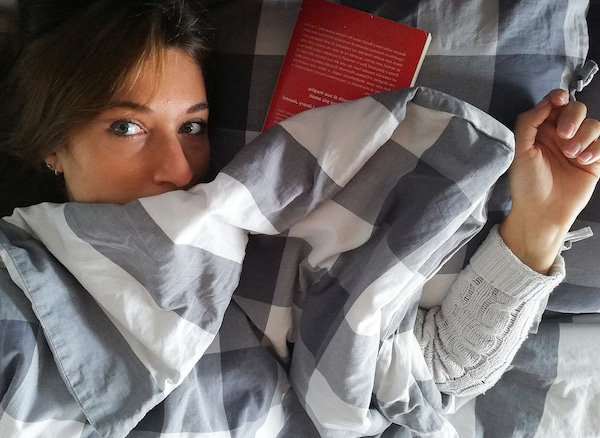 A woman with brown hair is lying underneath grey and white bedding. A red book is placed next to her head.