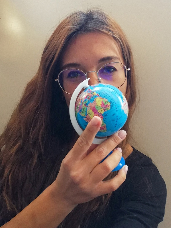 A woman with brown hair, wearing glasses is holding a small, plastic globe in front of her face.