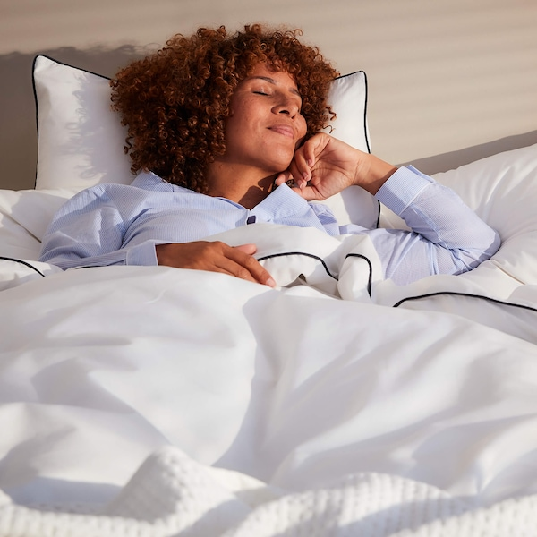 A woman with curly hair smiling while lying down on a bed with three pillows in white pillowcases and a white duvet.