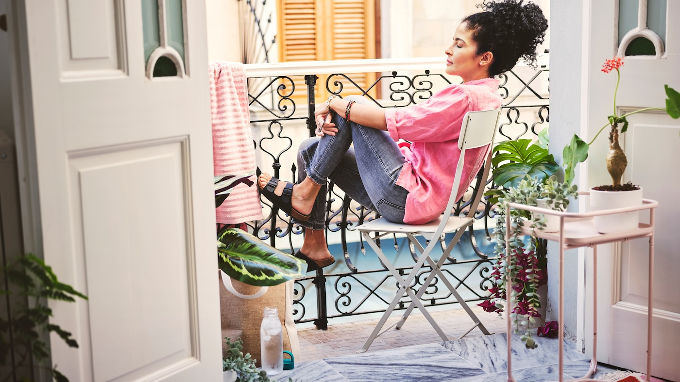 A woman with dark hair leans back and relaxes on a chair on a balcony. She is wearing a pink shirt and jeans.