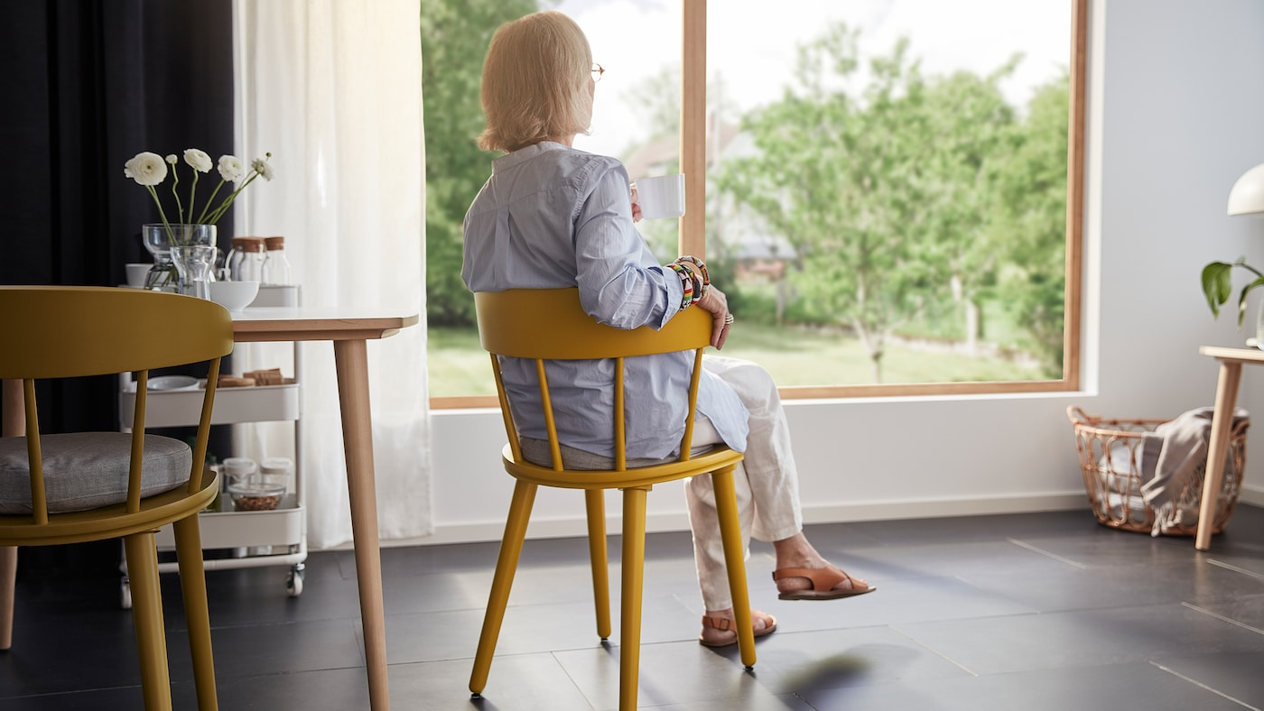 A woman with grey hair sits in a yellow chair in a room looking out through a big window.