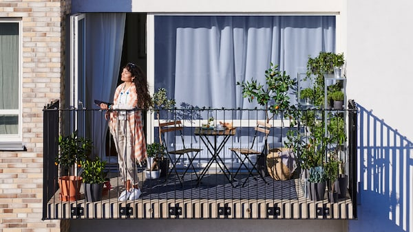 A woman with long dark hair stands on an apartment balcony that has potted plants and a small table with two chairs.