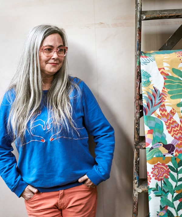 A woman with long grey hair in pink-framed glasses and blue sweatshirt next to brightly patterned fabric hung on a ladder.